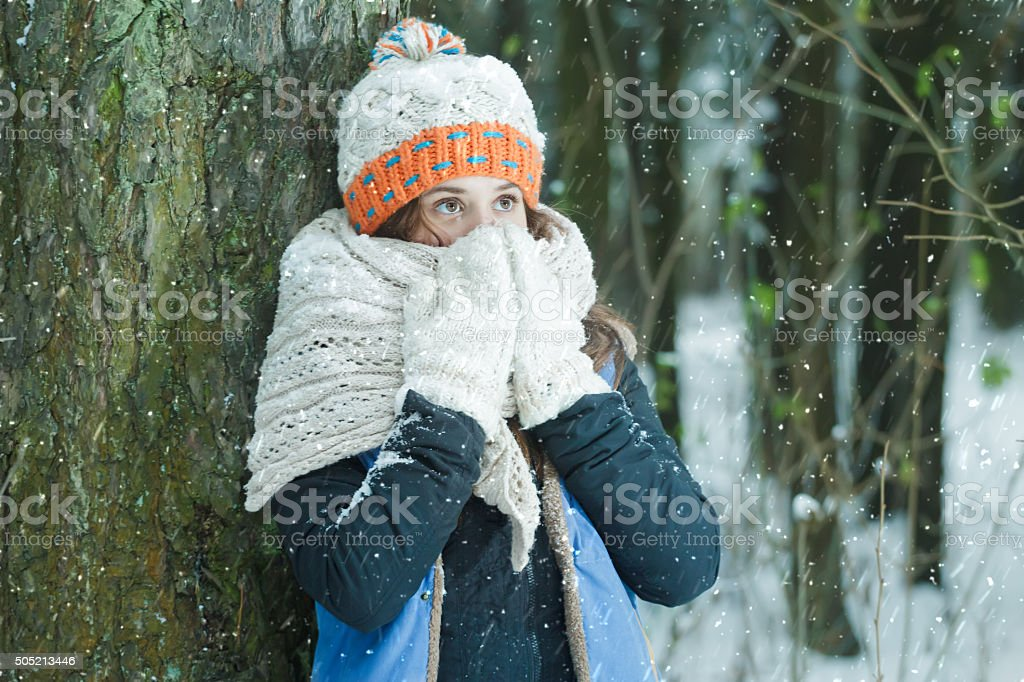 Girl hiding her face with wooly knitted bulky scarf outdoors stock photo