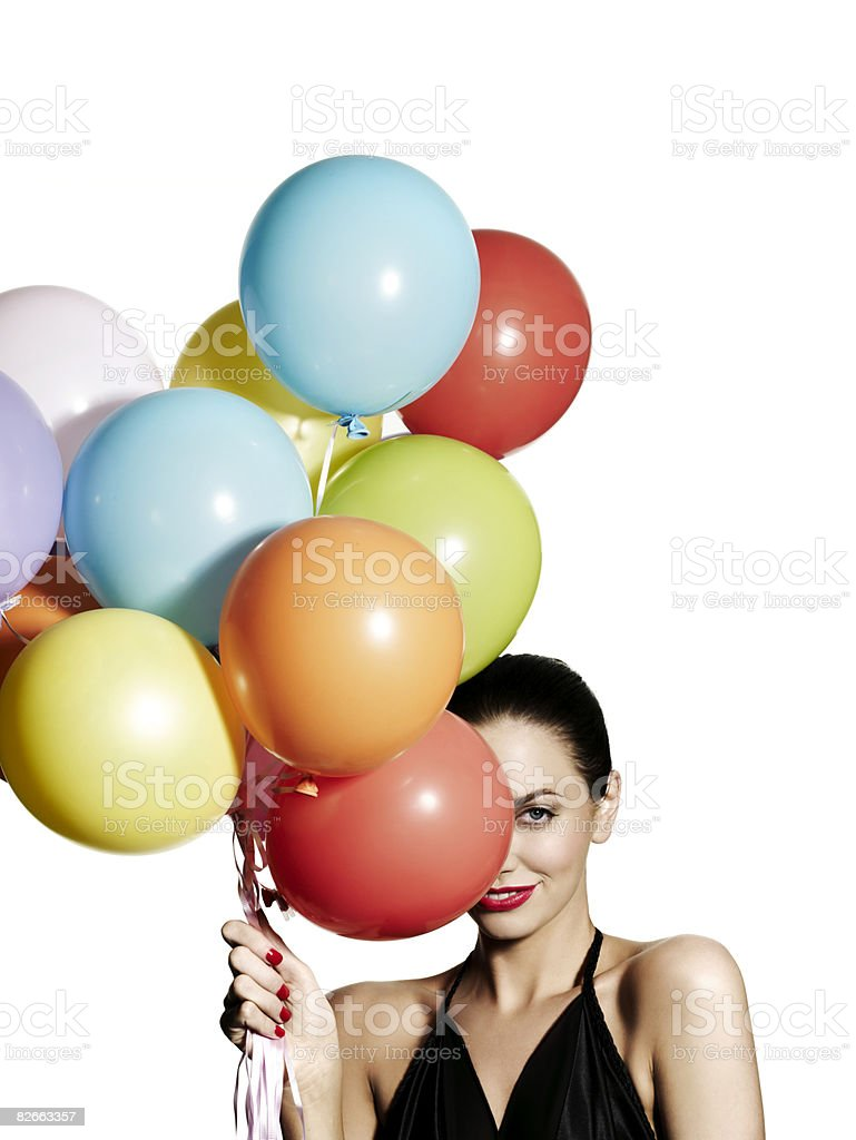 Girl hiding one eye behind a bunch of balloons stock photo