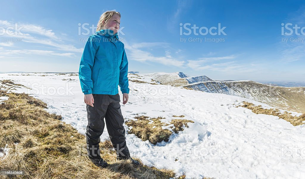 Girl hiker looking out over snow mountain wilderness panorama royalty-free stock photo