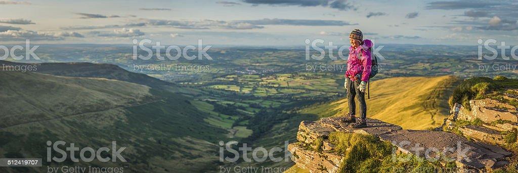 Girl hiker on idyllic mountain ridge looking at panoramic vista stock photo