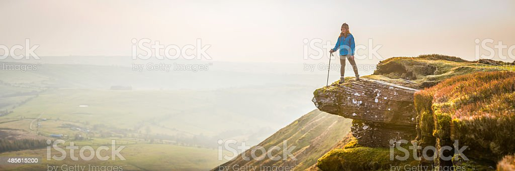 Girl hiker on mountain ridge overlooking misty valley sunrise panorama stock photo
