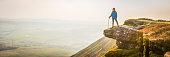 Girl hiker on mountain ridge overlooking misty valley sunrise panorama
