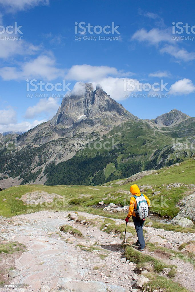 girl hiking with the Midi d'Ossau peak behind in France stock photo
