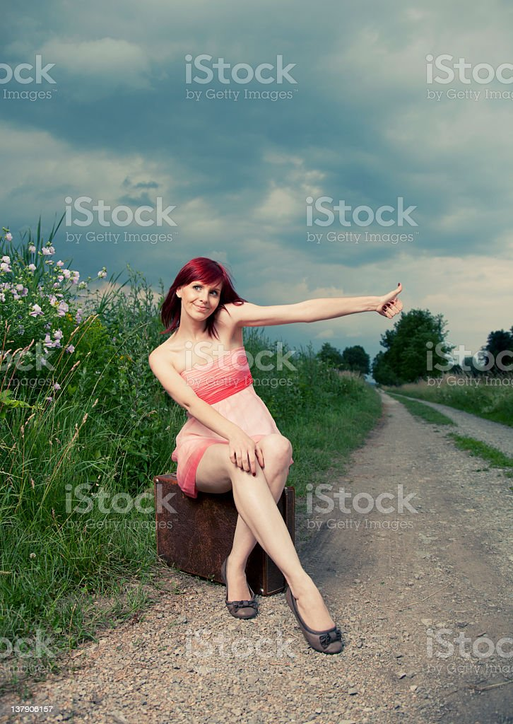 Girl hitchiking by the road stock photo