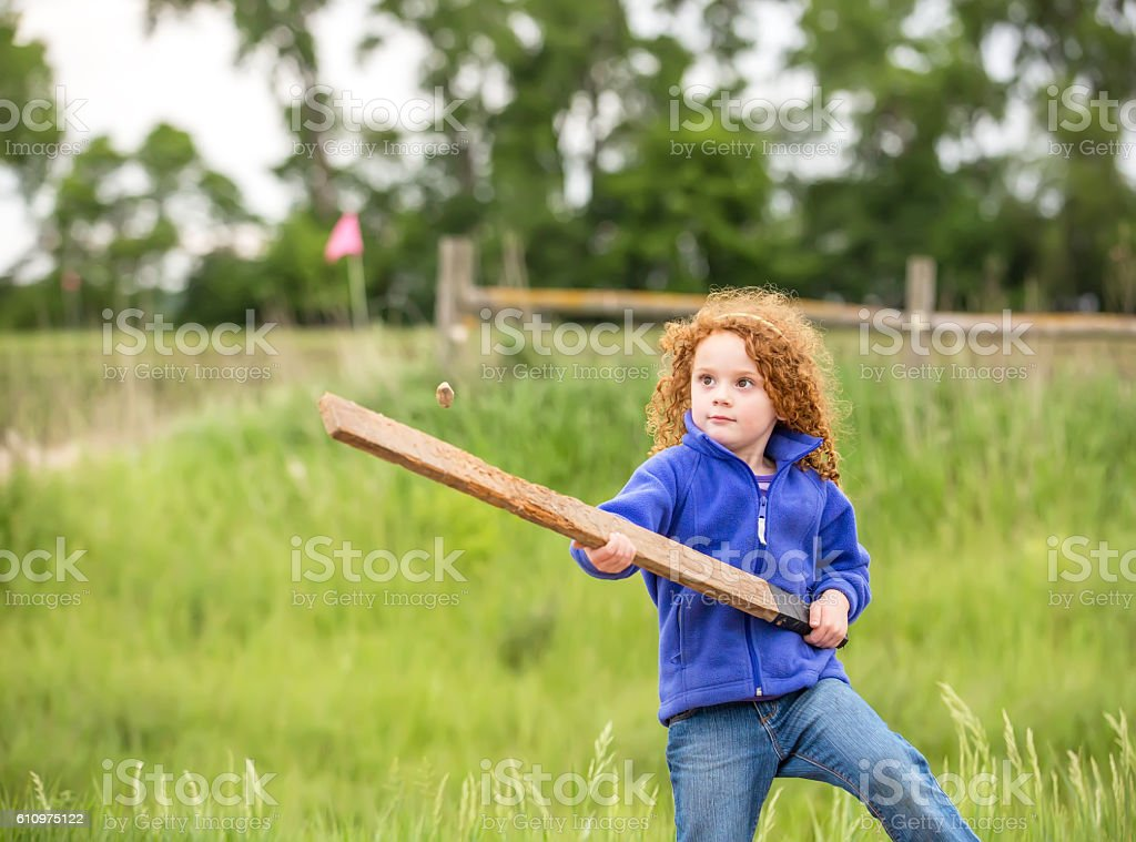 Girl Hitting Stone With Homemade Wood Board Bat stock photo