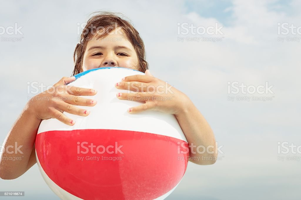 Girl holding a beach ball stock photo