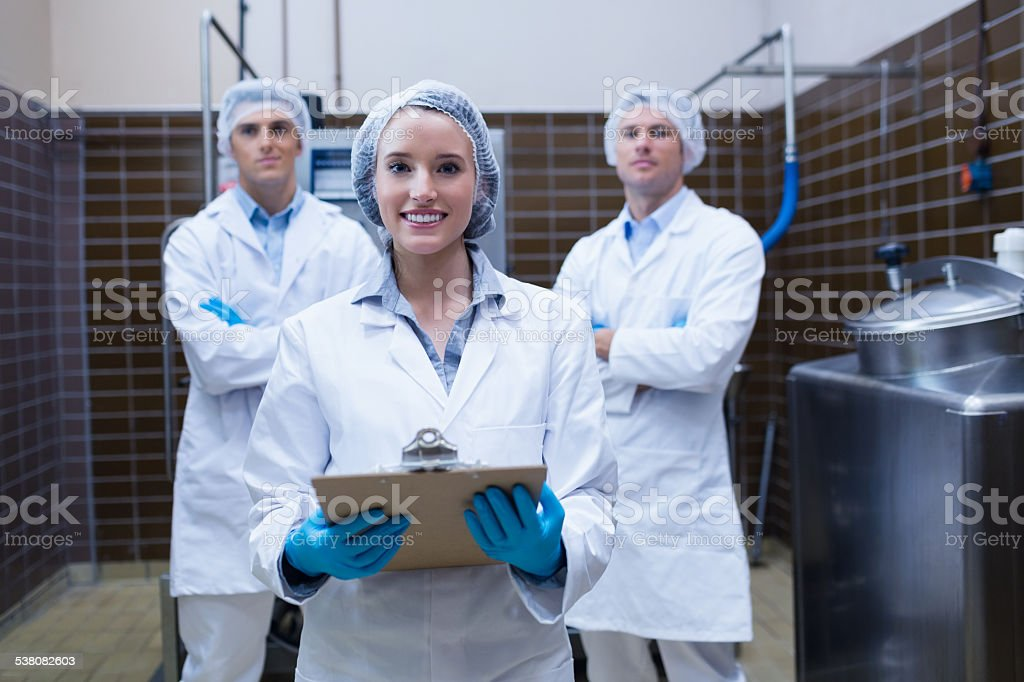 Girl holding a clipboard with these colleagues behind her stock photo