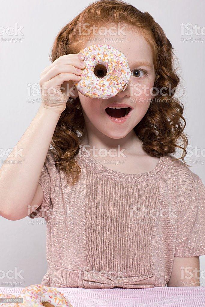 Girl holding a doughnut to her eye stock photo