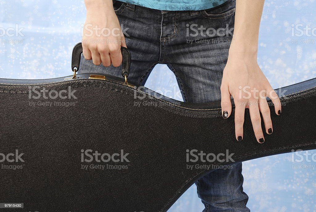 Girl holding a guitar case stock photo