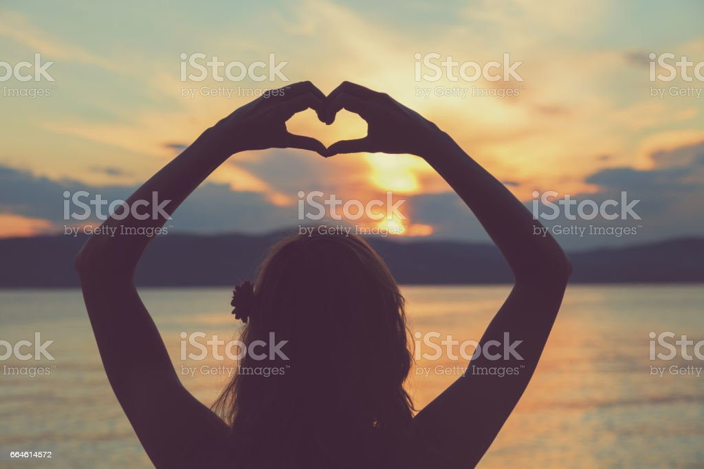 Girl holding a heart shape for the ocean / sea. stock photo