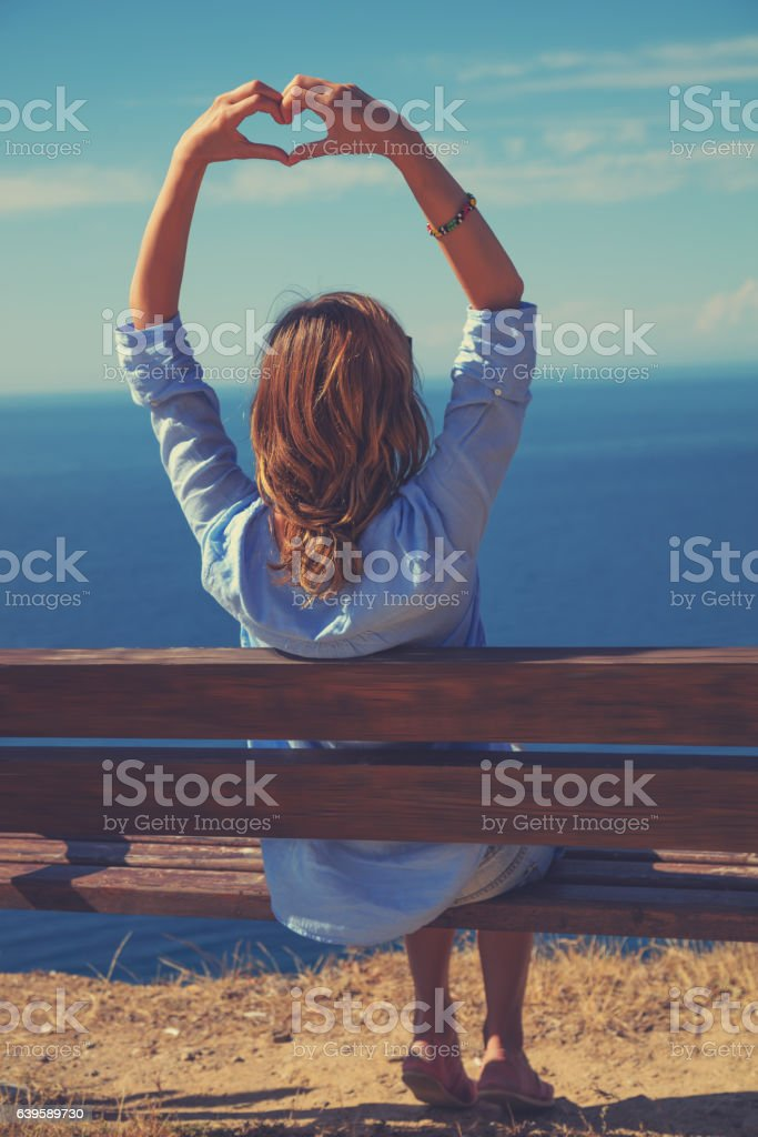 Girl holding a heart shape for the summer time. stock photo