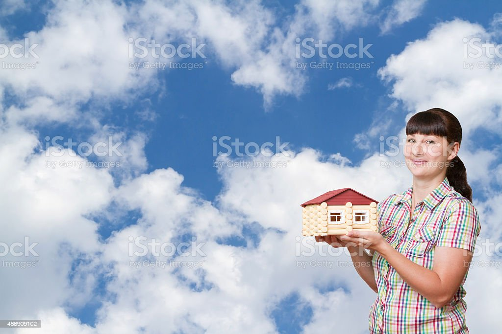 Girl holding a house on a background of sky stock photo