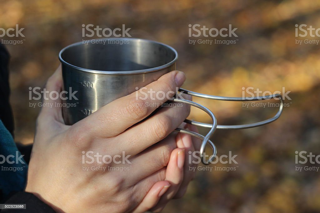 Girl holding a metal mug in autumn forest stock photo