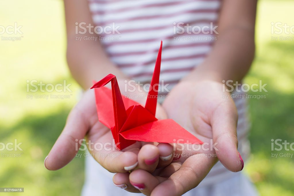 Girl holding a paper crane stock photo