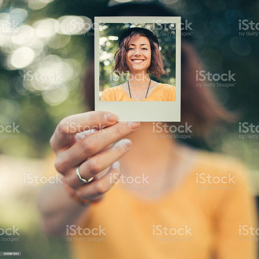 Girl holding a polaroid photo stock photo