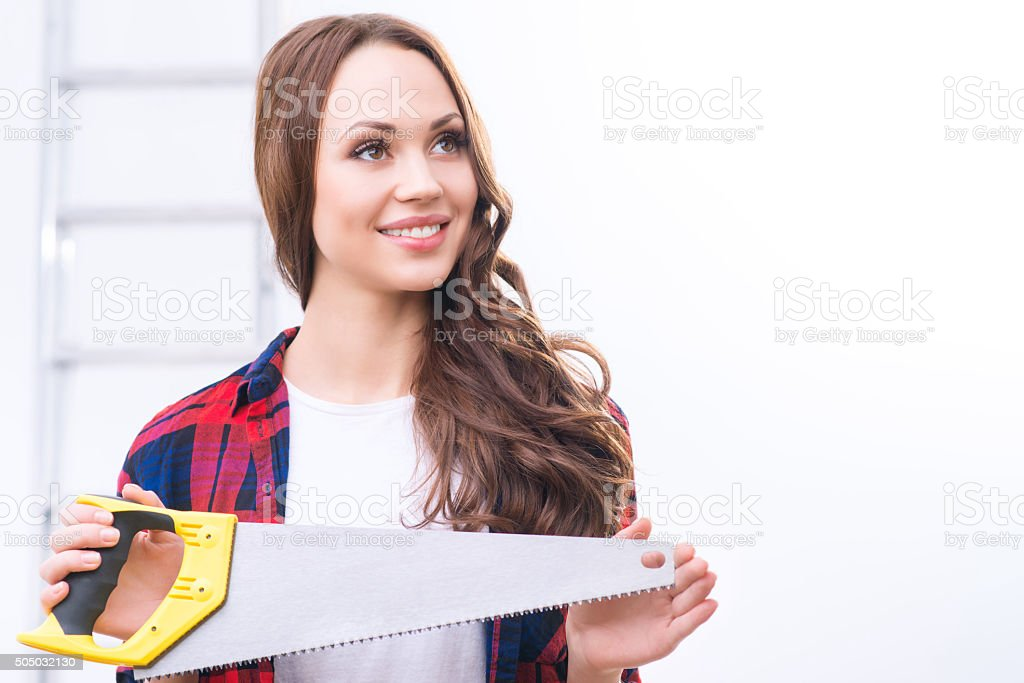 Girl holding a saw and looking up stock photo