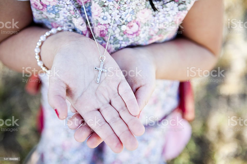 Girl holding a silver cross in her hands stock photo