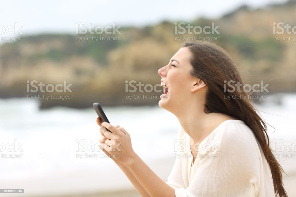 Girl holding a smart phone crying desperately stock photo