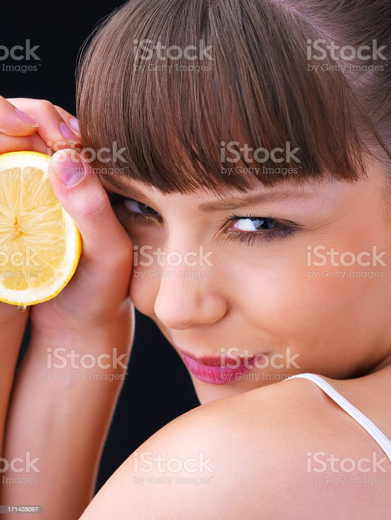 Girl holding a sour lemon stock photo