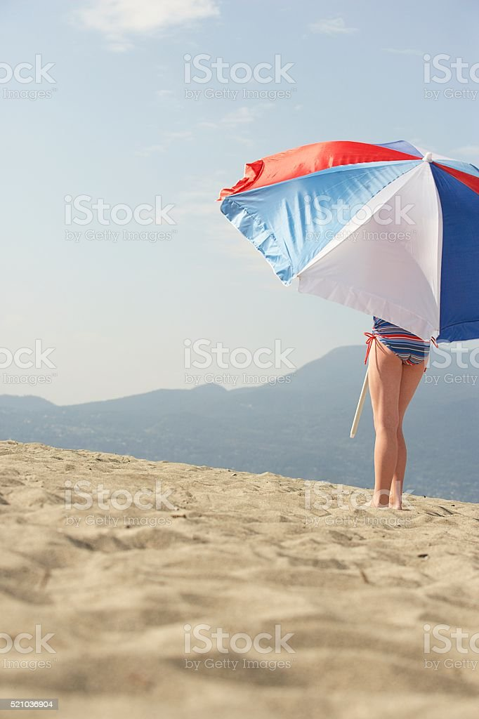 Girl holding an umbrella on the beach stock photo