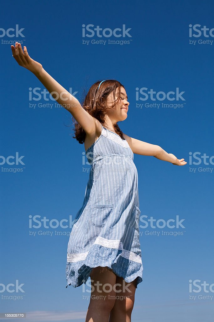 Girl holding arms up against blue sky royalty-free stock photo