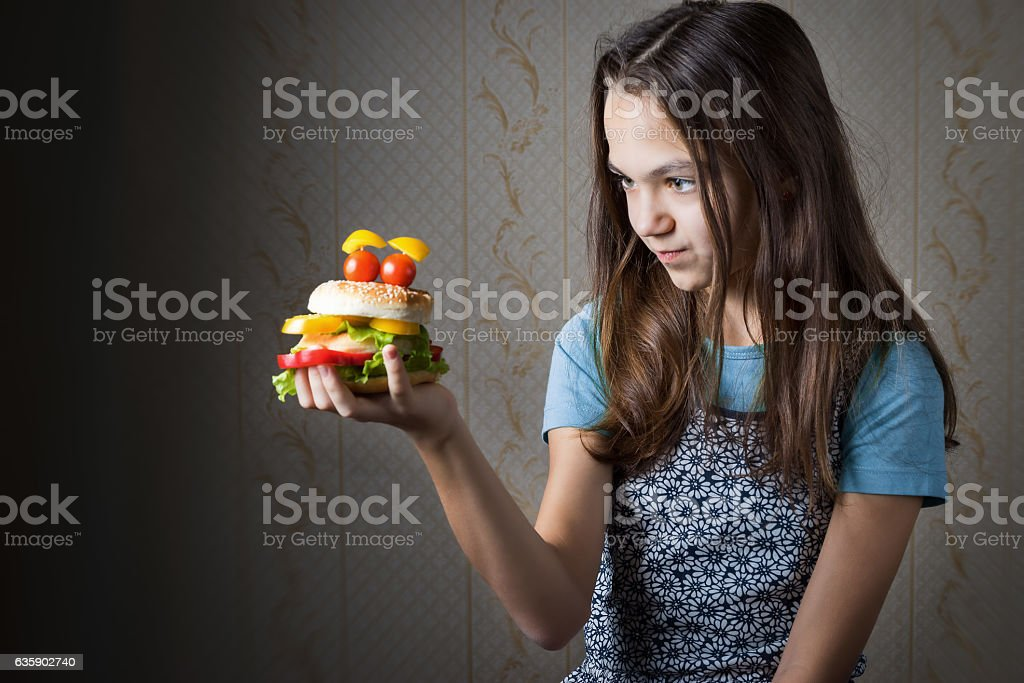 girl holding at arm hamburger decorated as smiley face stock photo