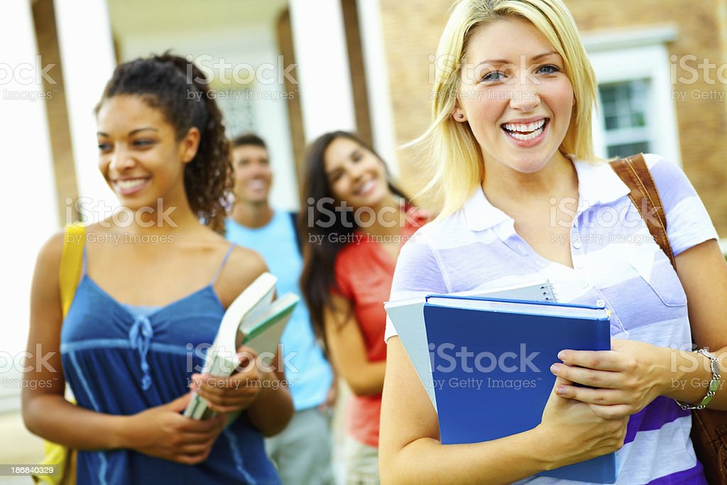Girl holding books with friends in background royalty-free stock photo