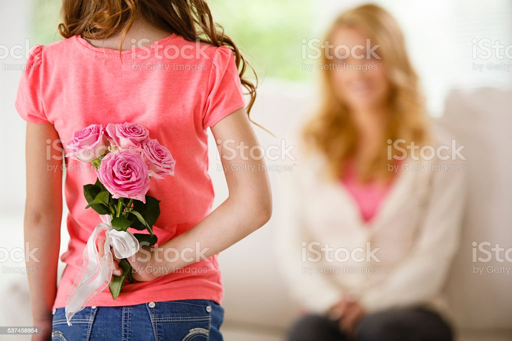 Girl holding bouquet of roses behind back, surprising mother stock photo