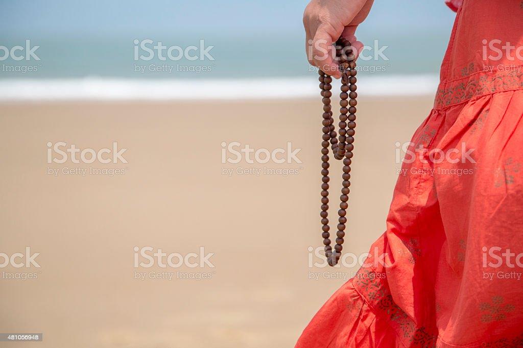 girl holding Buddhist beads on the beach stock photo