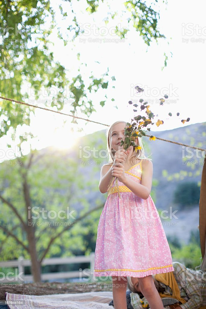 Girl holding bunch of flowers on blanket royalty-free stock photo