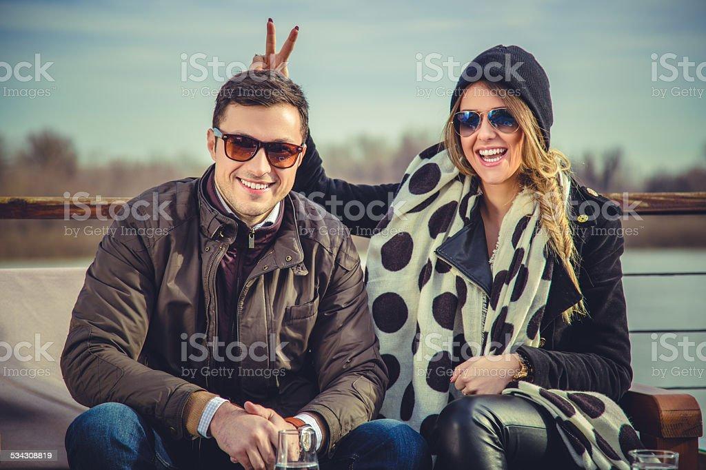 Girl holding bunny ears to her boyfriend stock photo