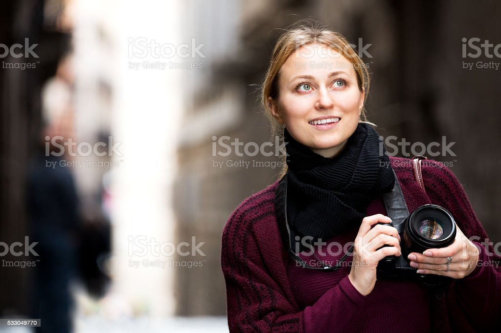 Girl holding camera in hands and photographing stock photo