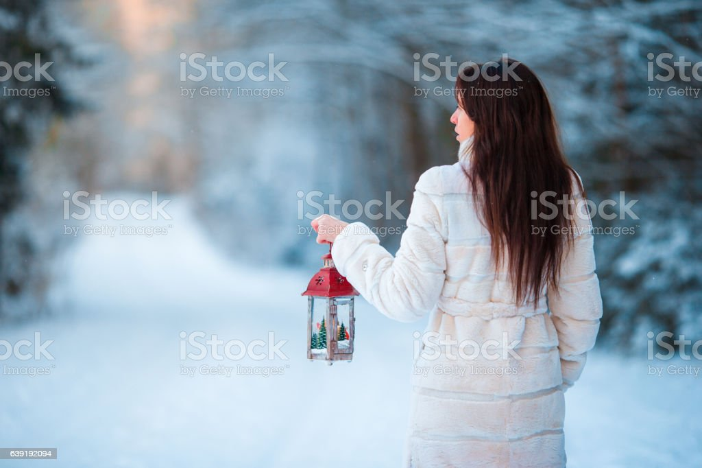 Girl holding Christmas lantern outdoors on beautiful winter snow day stock photo