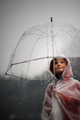 Girl holding clear umbrella looking at rain