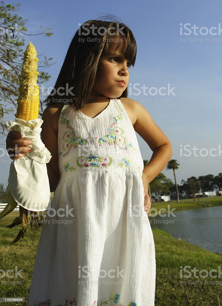 Girl holding corn on the cobb stock photo