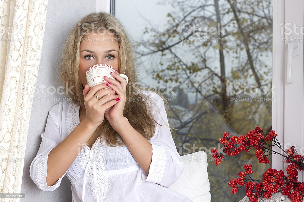 girl holding cup and looking through window stock photo