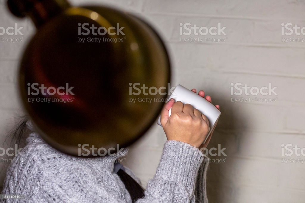 girl holding cup drinking water under lamp stock photo