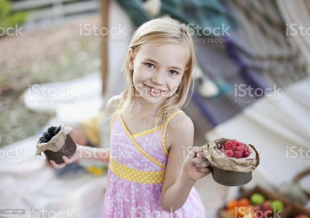 Girl holding cups of fruit outdoors royalty-free stock photo