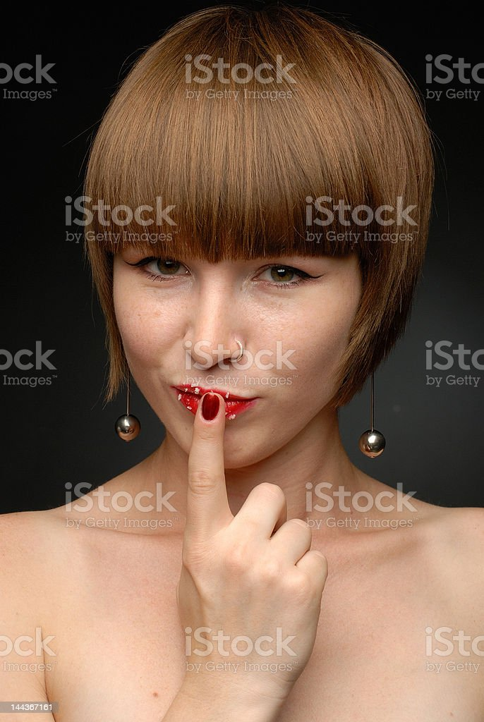 Girl holding finger to her lips with crumbs looking straight royalty-free stock photo