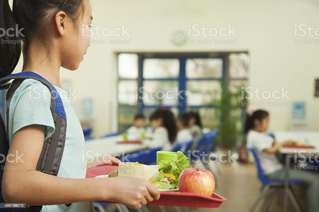 Girl holding food tray in school cafeteria stock photo