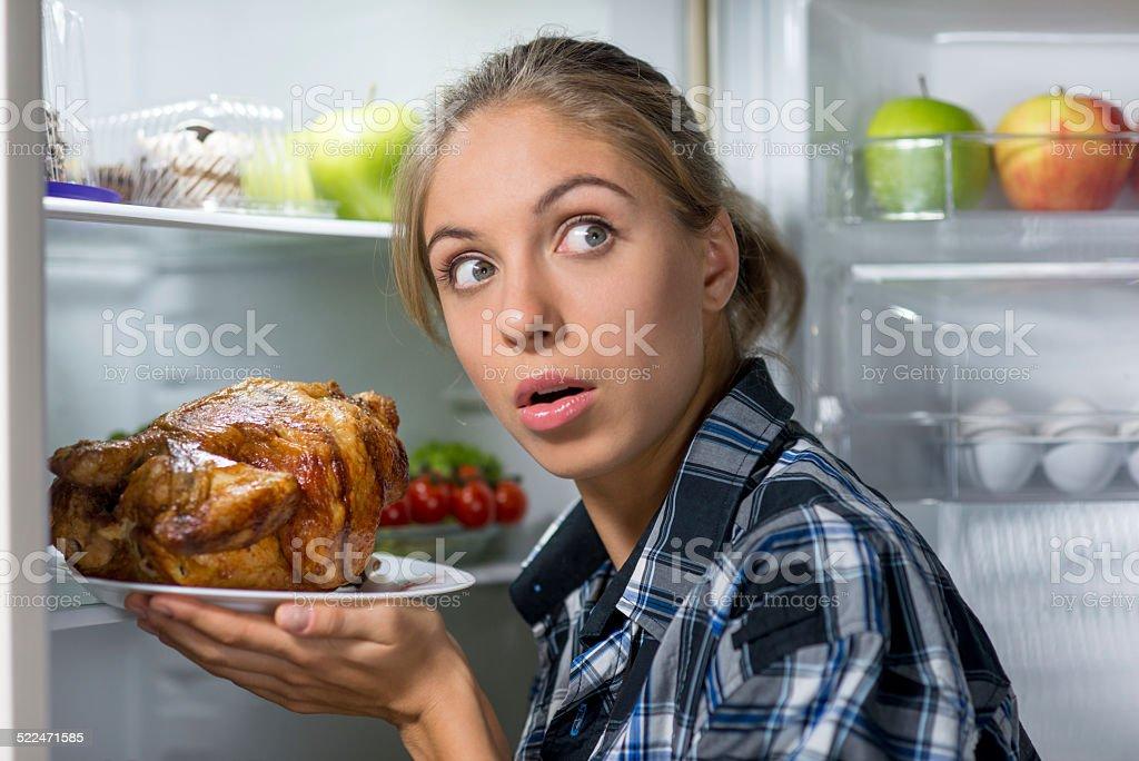 Girl holding fried chicken near opened refrigerator stock photo