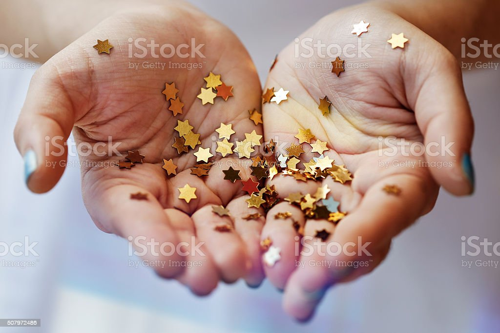 Girl holding gold star confetti stock photo