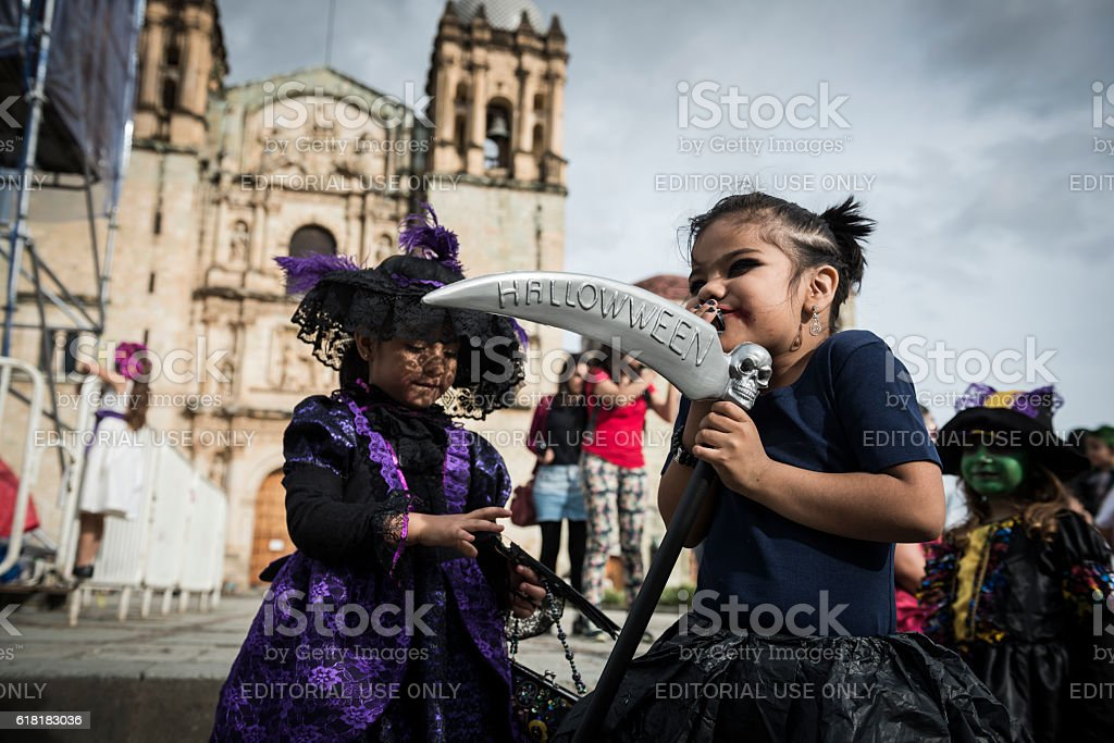 Girl holding grim reaper scythe with Halloween text in Mexico stock photo