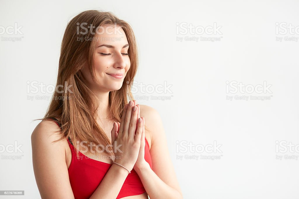 Girl holding hands in namaste. stock photo