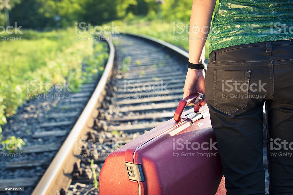 Girl Holding Her Bag Against The Railroad At Sunset royalty-free stock photo