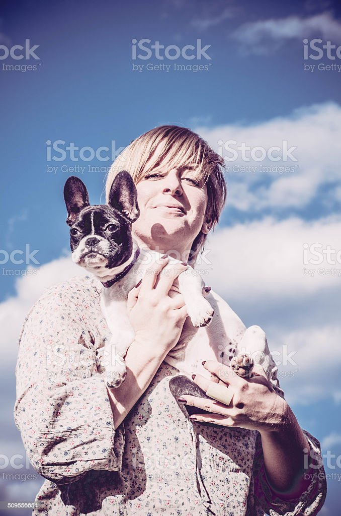 Girl holding her French Bulldog in the Sky stock photo