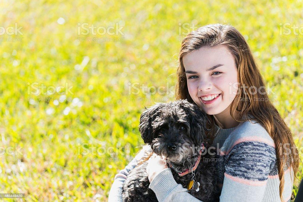 Girl holding her pet dog stock photo