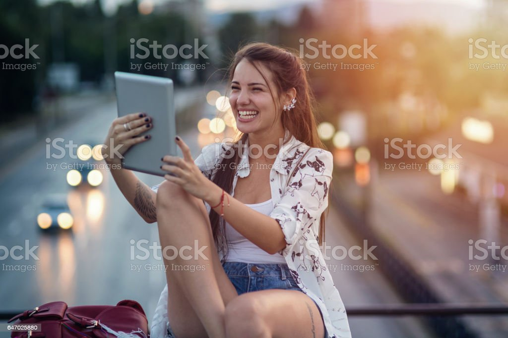 Girl holding her tablet and laughing stock photo