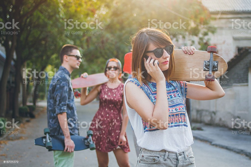Girl holding longboard and talking on the phone stock photo