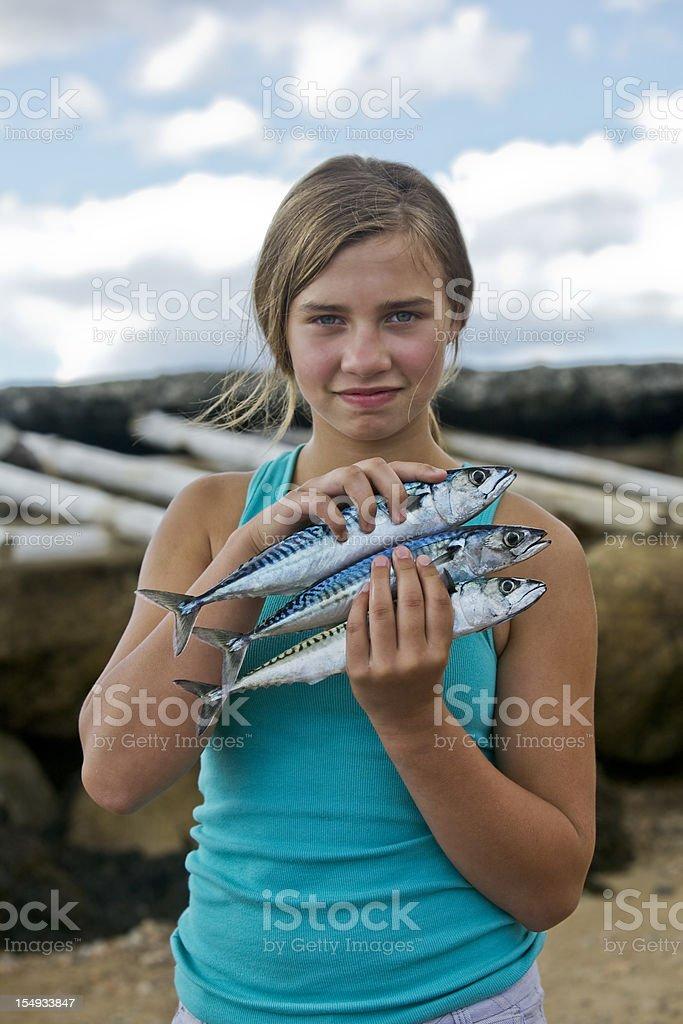 Girl holding Mackerel fish that she caught stock photo